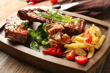 Wooden board with delicious grilled ribs and french fries on table