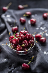 Sweet ripe cherries on dark tablecloth with water drops