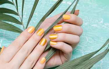 Female hands with orange nail design