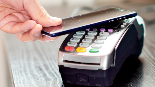 Customer paying with NFC technology by mobile phone on POS terminal.