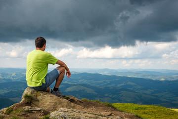man sitting on the peak of the mountain