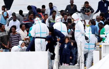 "Migrants wait to disembark the Italian coast guard vessel ""Diciotti"" as they arrive at the port of Catania"