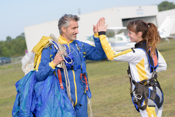Parachutists high fiving after jump