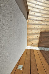 Ciment wall and insulating wood cladding in outdoor courtyard