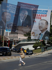 A woman walks under elelction posters for Turkey's President Tayyip Erdogan and Muharrem Ince, Presidential candidate of Turkey's main opposition Republican People's Party (CHP)  in Istanbul