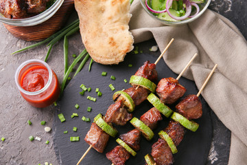Barbecue skewers with juicy meat and squash on slate plate