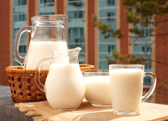 A lot of milk on the windowsill. Milk in jugs and a mug on the balcony sill. Breakfast on the background of city windows.