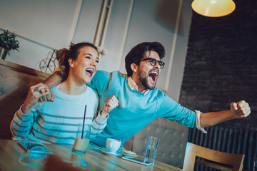 Modern couple in cafe looking excited and happy after their favorite football team scored a touchdown.
