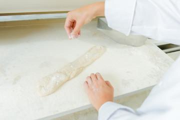 Dusting a baguette with flour