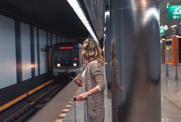 Young woman with suitcase waiting train in metro station.