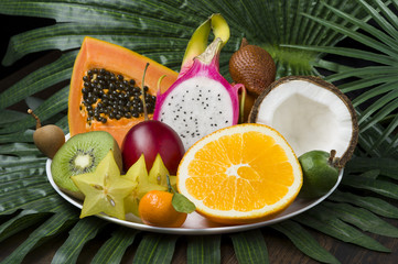 Fresh Thai fruits dish on palm leaves and wooden background, healthy food, diet nutrition, selective focus