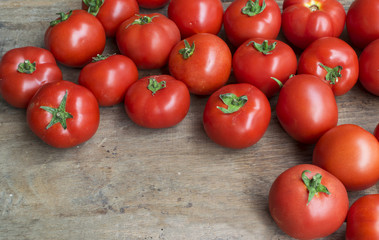 Fresh, red tomatoes on old wooden background