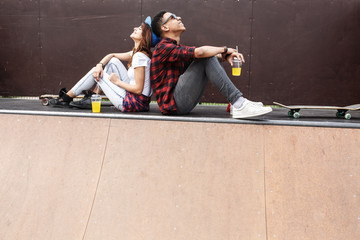 Couple of teenagers skaters sitting on ramp and hangout at the skate park .Laughing and fun.