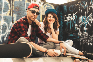Young teen couple sitting by the wall and hangout at the street .Embrace each other and laughing .
