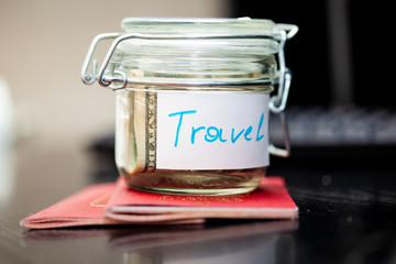 Holidays money savings in a glass jar. Two passports are next to money box. Journey or travel concept