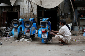 A man repairs a Vespa scooter at workshop in Karachi