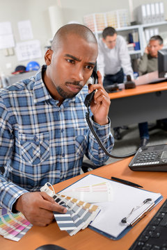 Man on telephone holding colour charts, looking confused
