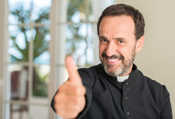 Christian priest man happy with big smile doing ok sign, thumb up with fingers, excellent sign