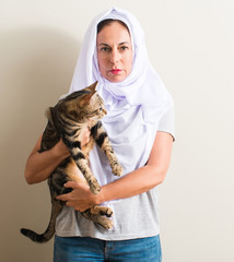 Arabian woman wearing white hijab holding a cat with a confident expression on smart face thinking serious