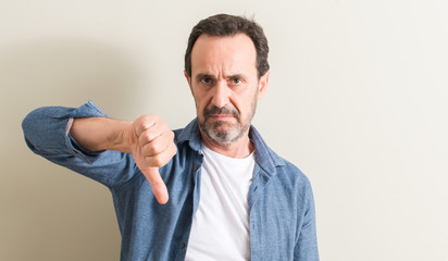Senior man with angry face, negative sign showing dislike with thumbs down, rejection concept