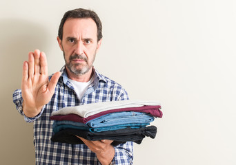 Senior man holding folded laundry clothes with open hand doing stop sign with serious and confident expression, defense gesture