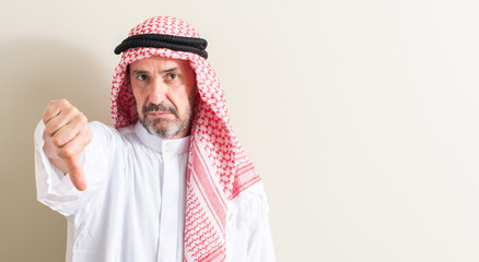 Senior arabic man with angry face, negative sign showing dislike with thumbs down, rejection concept