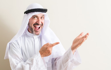 Senior arabic man very happy pointing with hand and finger