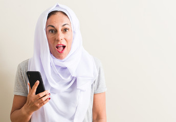 Arabian woman using smartphone scared in shock with a surprise face, afraid and excited with fear expression