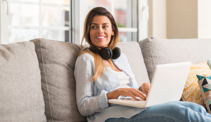Young beautiful woman smiling using laptop and listening to music with headphones on the sofa relaxed.