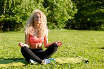 Image of young curly-haired sports woman practicing yoga on rug in park