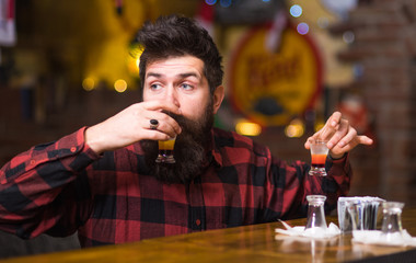 Hipster holds glass with alcoholic drink, short cocktail
