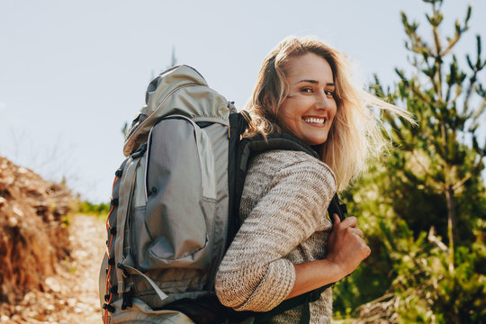 Woman with backpack hiking in nature