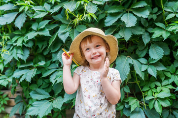 Little girl in straw hat with yellow pencil on background green plant leaves in garden summer.