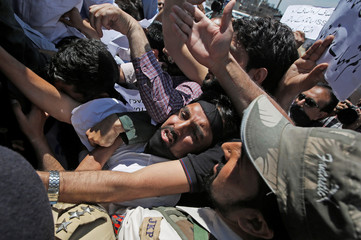 Teachers scuffle with an Indian policemen during a protest demanding the release of their pending salaries in Srinagar