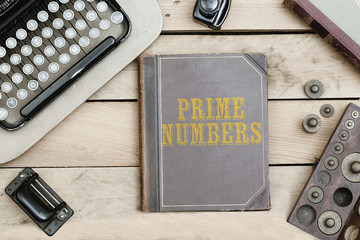 Text Prime Numbers on old book cover at office desk with vintage items