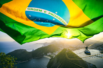 Brazilian flag shines above the golden sunset city skyline at Sugarloaf  Mountain in Rio de Janeiro Brazil.