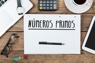 Spanish Text numeros primos (prime numbers) on note pad at office desktop
