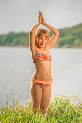 little girl with light hair standing in a swimsuit in the summer against a river