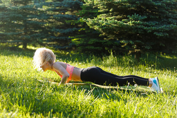 Photo of young curly-haired sports woman practicing yoga on rug in park