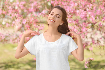 Beautiful young woman near blooming tree in park on spring day
