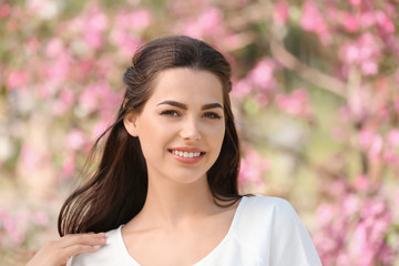 Beautiful young woman in park on spring day
