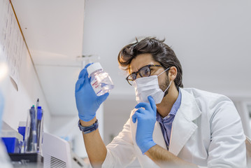Medical doctor in protective gloves and surgical mask  looking at small flask with liquid in laboratory. Scientific research, healthcare and medical concept.
