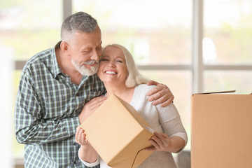Mature couple with moving boxes at new home