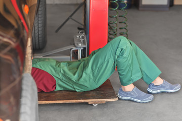 Auto mechanic repairing car in service center