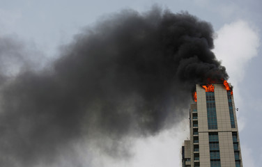 A fire is seen on top of a high-rise residential building in Mumbai