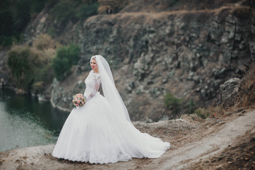 A beautiful bride in a lace dress with a long veil stands against the background of rocks and stones. Autumn wedding portrait of a cute bride.