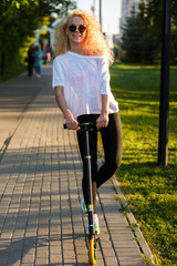 Photo of curly-haired athletic woman riding scooter in park