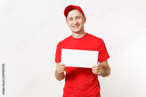 676465f1 Delivery man in red uniform isolated on white background. Male fun courier  in cap, t-shirt, jeans holding white empty blank paper. Copy space  advertisement.