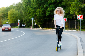 Full-length photo of curly-haired athletic woman kicking on scooter in park