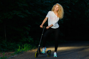 Full-length image of curly-haired athletic woman kicking on scooter in park